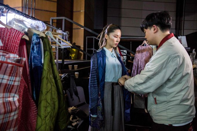 man helping woman dress behind scenes of fashion show in hong kong
