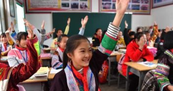 children raising hands in classroom in china