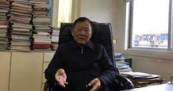 wang mengshu sitting in chair at desk in office