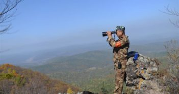 side view of man on hill looking through binoculars