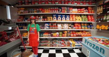 owner standing in supermarket with artistic food made from fabric
