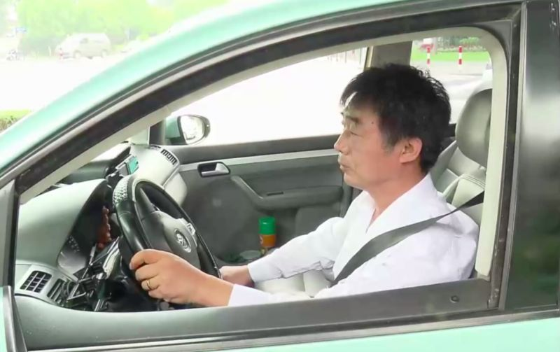 side view of taxi driver behind wheel in china