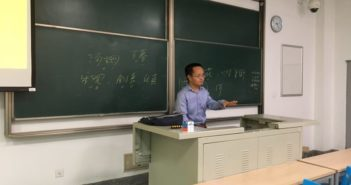 university teacher sitting at front of class