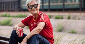 old lady sitting outside drinking coke