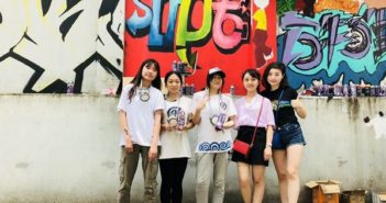 students posing for picture in from of graffiti