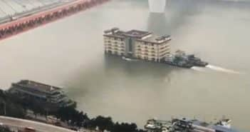 multistoried restaurant being pushed by boats on river in chongqing