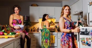 three women wearing colourful dresses in a kitchen