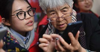 younger woman showing old woman a smartphone in china