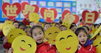 primary school students holding smiley faces