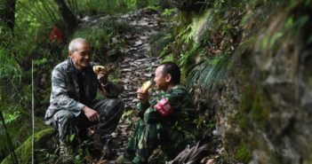 two forest rangers eating in forest in china