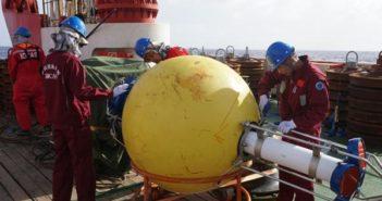 workers on science vessel preparing buoy