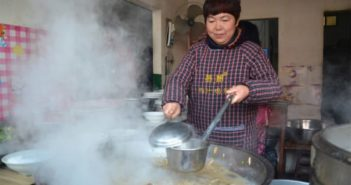 woman cooking in big pot at restaurant in china