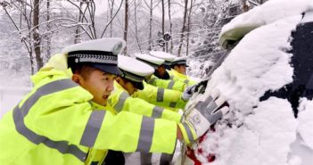 policemen pushing car in the snow