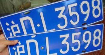 hand holding 2 shanghai car plates