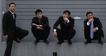 4 men in suits outside thinking