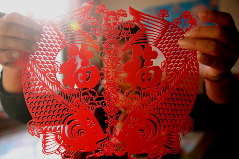 woman holding up paper cutting art in china