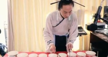 man making music with bowls and chopsticks
