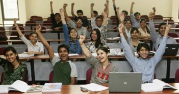 students with arms in the air in classroom at indian university