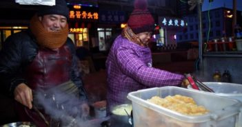 couple cooking at night market food stall in harbin