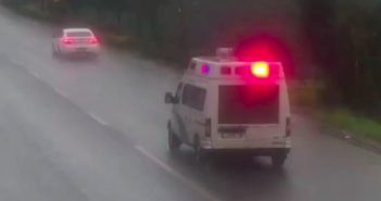 back view of police van chasing car down road in china