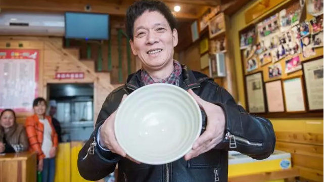 man holding empty bowl at restaurant in china