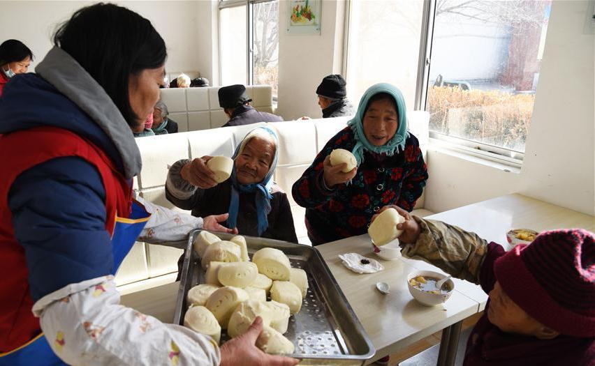 woman giving elderly women baozi at restaurant in china
