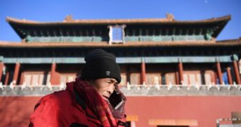 side view of man on phone next to forbidden city in beijing