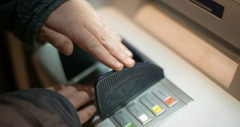hands inputting pin at atm
