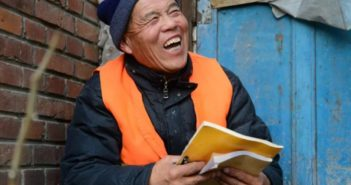sanitation worker holding a notebook and laughing
