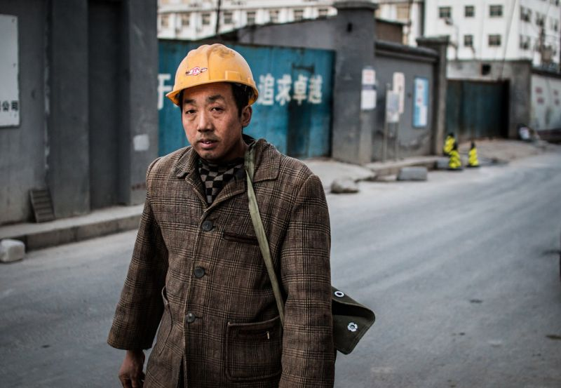 man in hard hat walking down street
