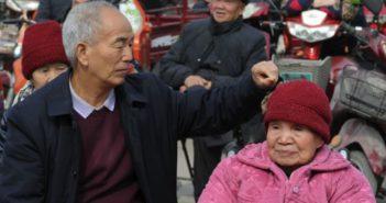 elderly son picking at elderly mother's hat