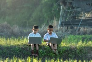 two young boys sitting outside in countryside on computers
