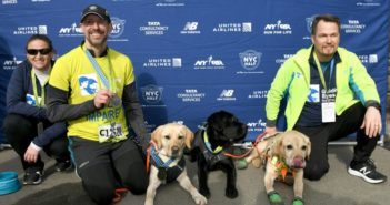 blind runner posing for picture with guide dogs after marathon on new york