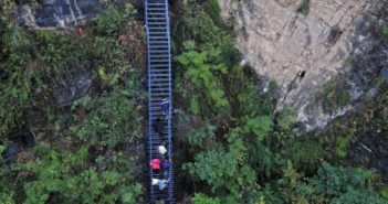 people climbing steel ladder on side of cliff in china