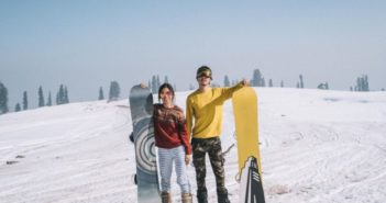 couple posing for picture with snowboards