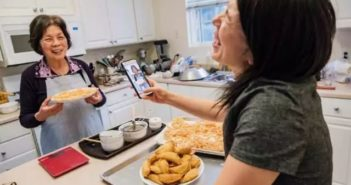 woman taking picture of grandma cooking