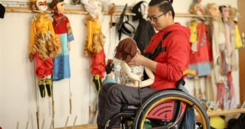 man in wheelchair with a puppet