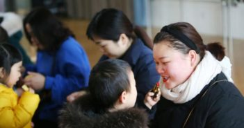 students helping mothers put on make up at kindergarten in china