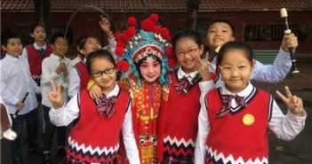 girl in beijing opera outfit posing for picture with classmates