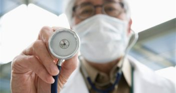 doctor with face mask holding stethoscope