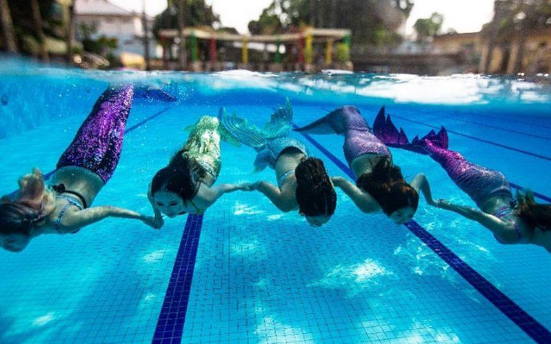 girls swimming in pool wearing mermaid tails