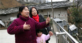 woman holding phone to make video in chinese village