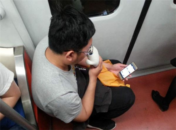 top view of man sitting on stool on shanghai metro train