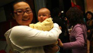 china's first test-tube baby holding newborn baby