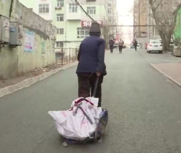 back view of elderly woman walking down the street in china