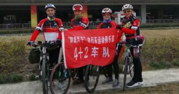 four senior cyclists posing for picture on side of the road