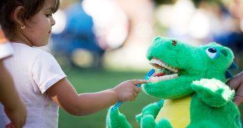 girl brushing toy crocodile's teeth