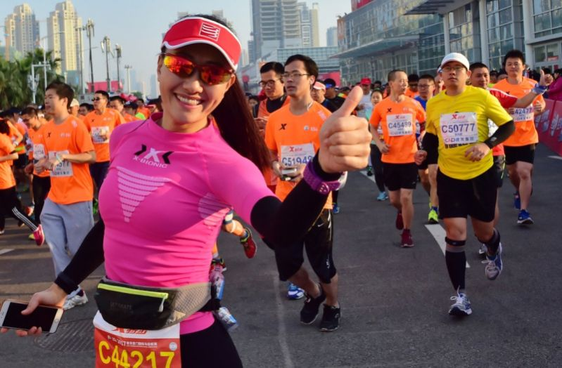 woman giving thumbs up during marathon in china