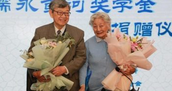 elderly couple holding flowers at event