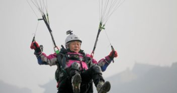front view of elderly woman paragliding in china